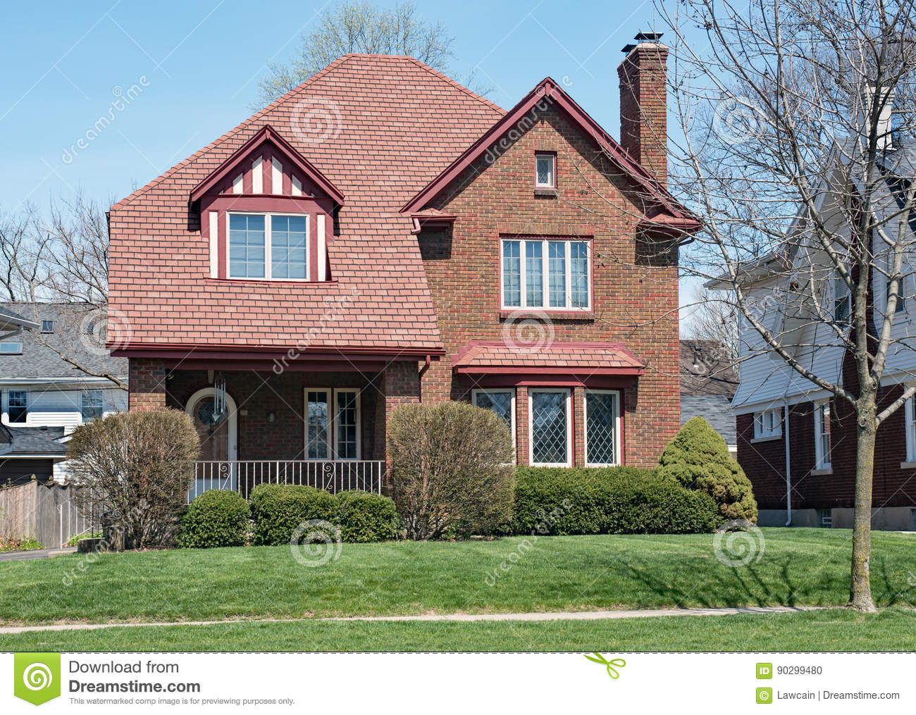 Brick House With Red Shingle Roof Stock Photography