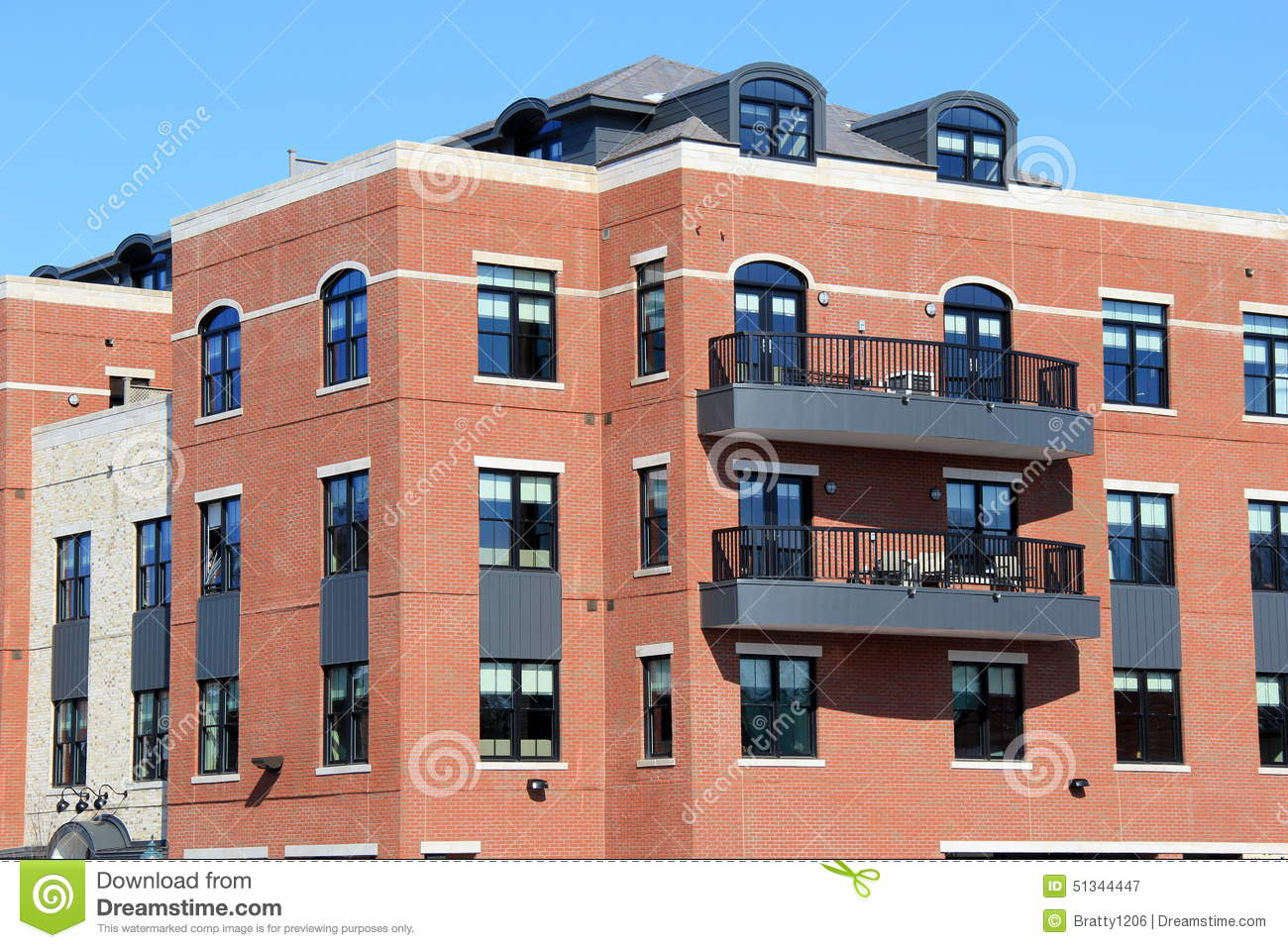 brick and stone apartment building with outdoor patios