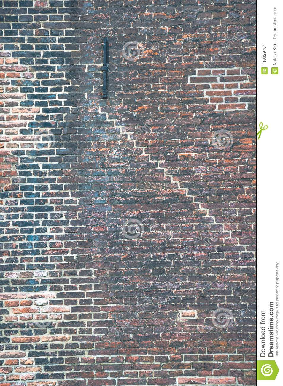 Brick wall with many layers of old paint and different patterns