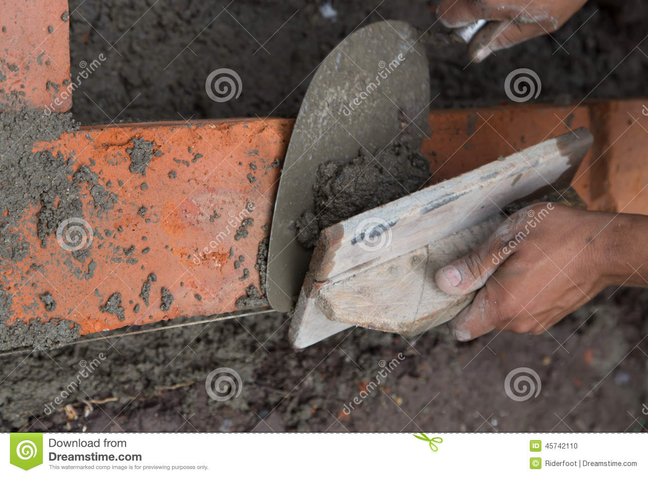 Bricklayer Building A House Using Tools And Cement Stock