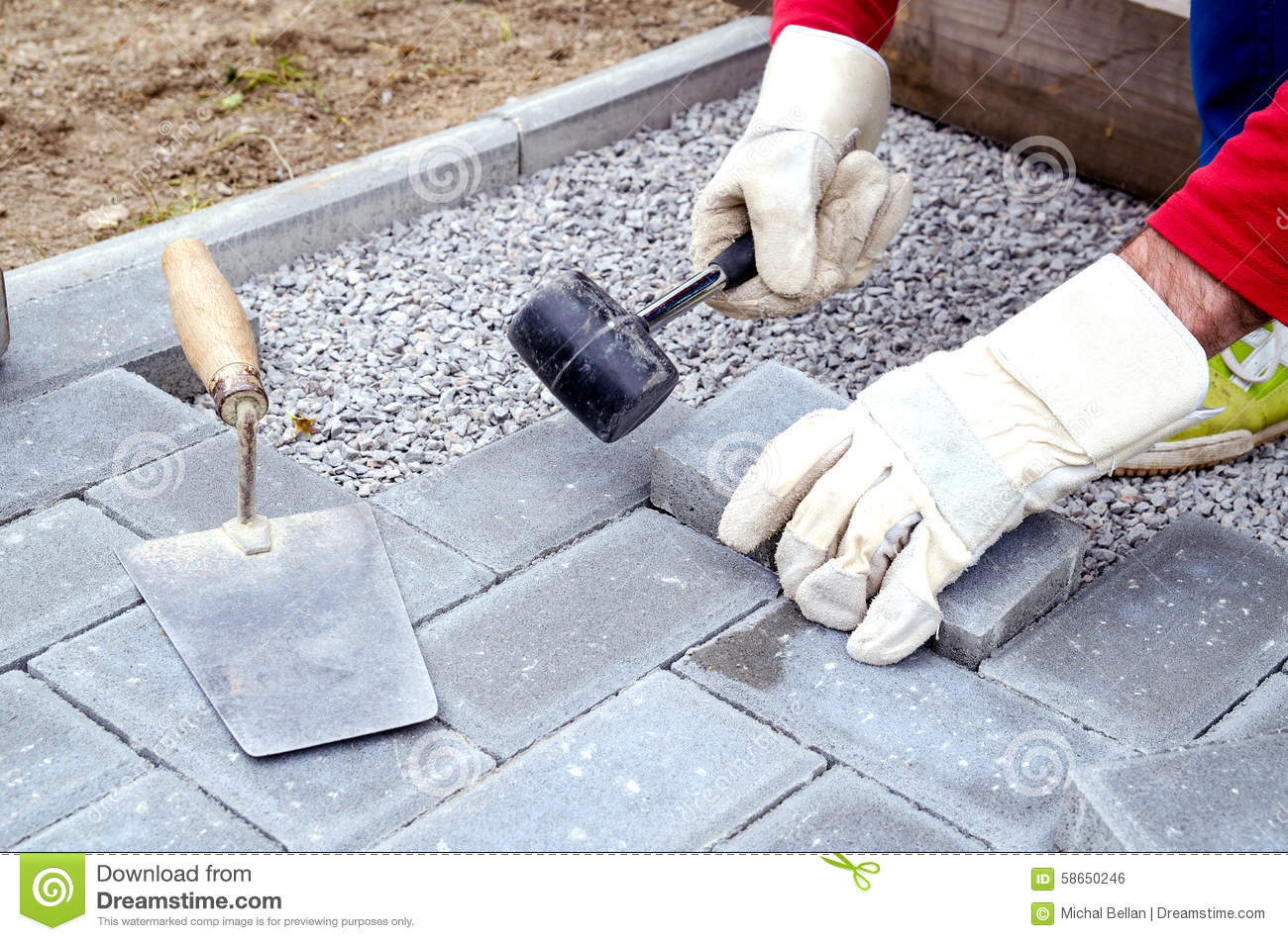 Bricklayer Places Concrete Paving Stone Blocks For Building Up A Royalty  Free Stock Image