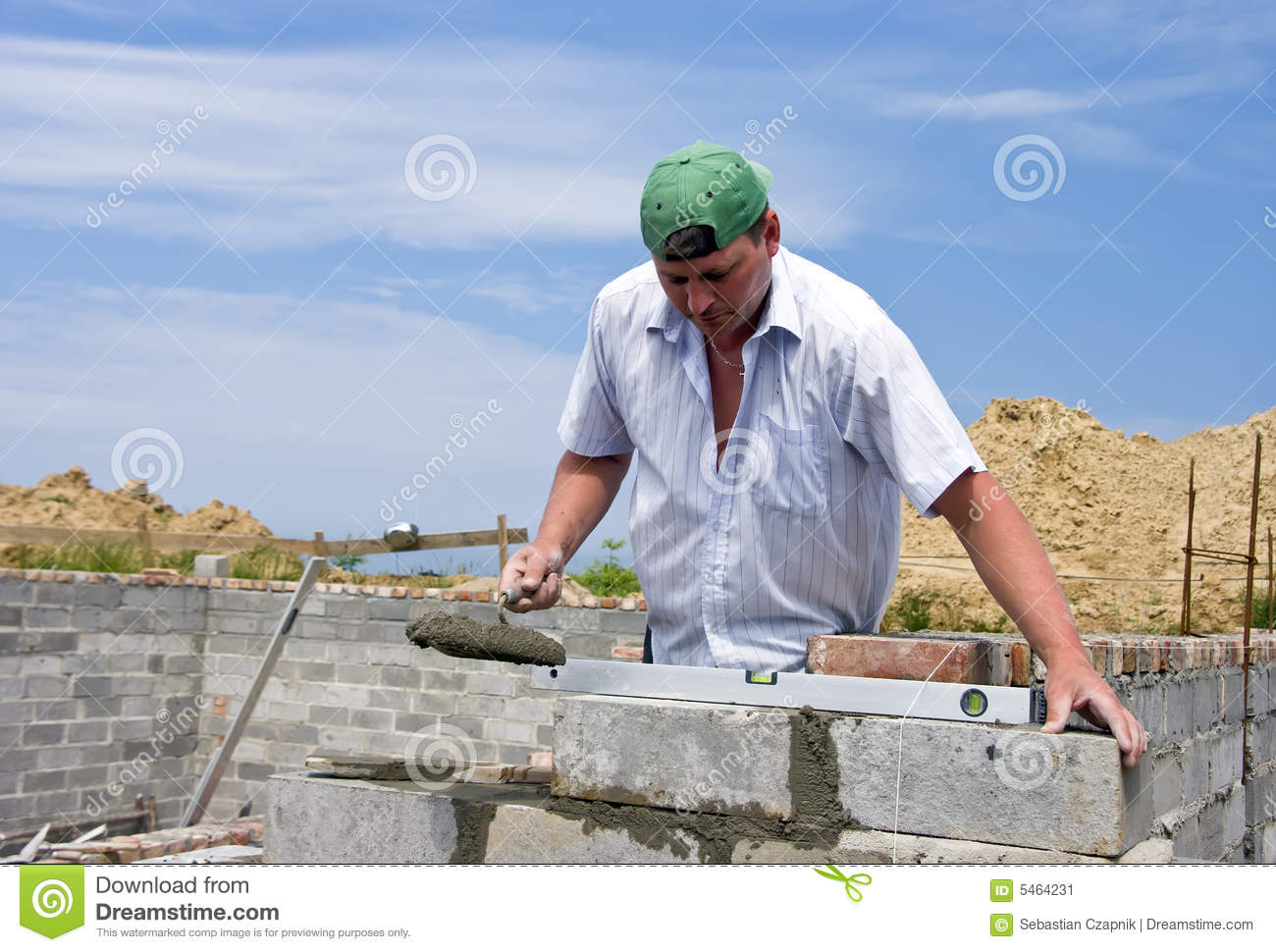 House builder bricklayer at work he is using his trowel to lay