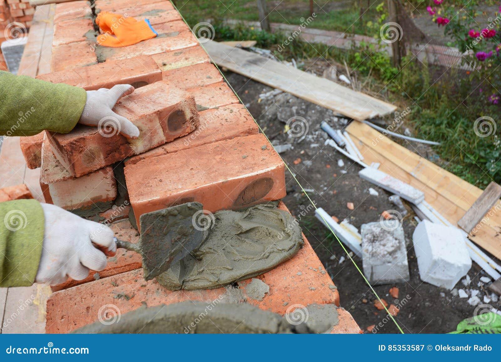 Bricklaying Bricklayer Worker Installing Red Blocks And Caulking Brick Masonry Joints Exterior