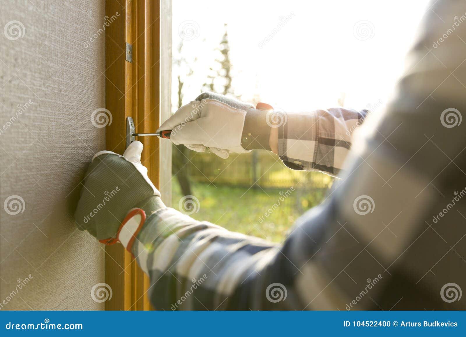 Bricoleur fixant la fenêtre avec le tournevis