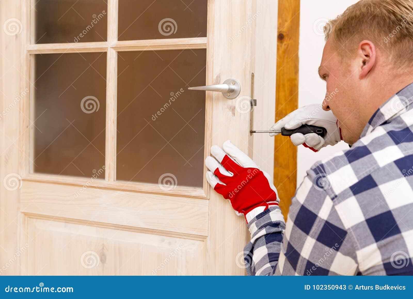 Bricoleur fixant la porte avec le tournevis