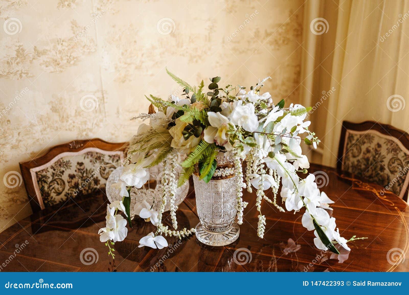 Bridal букет в шикарной кристаллической вазе на высекаенном отлакированном конце-вверх деревянного стола