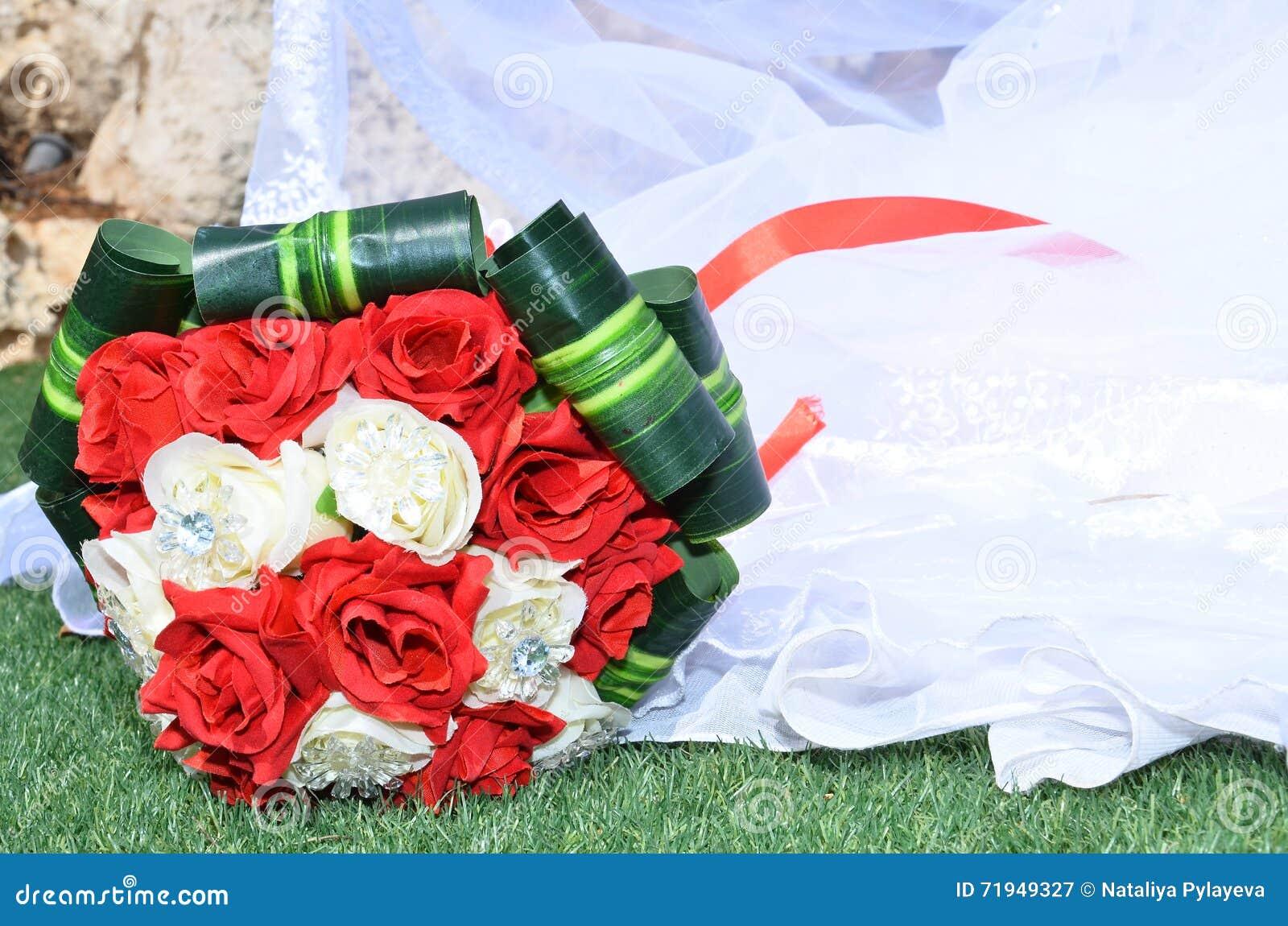 Bridal букет шарлаха и белых роз с зелеными листьями на кромке платья свадьбы