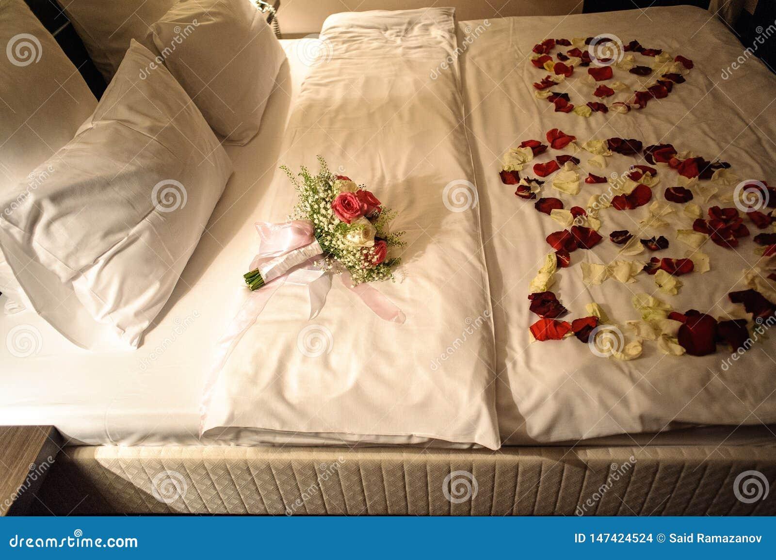 Bridal bukiet i różani płatki na łóżku z białymi pościelami