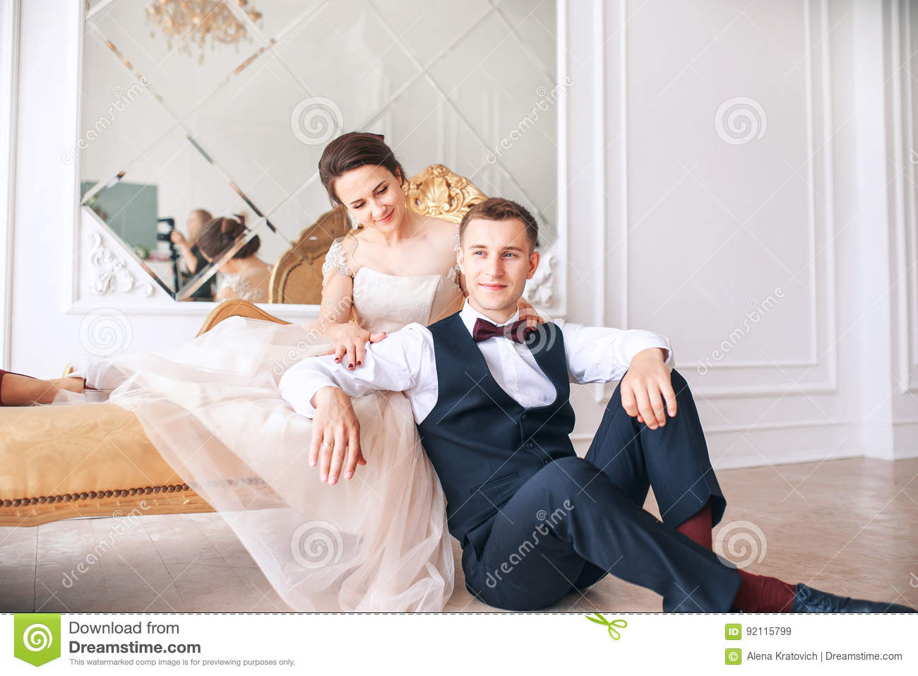c160aaba6d1 Bride in beautiful dress and groom in black suit sitting on sofa indoors in  white studio interior like at home. Trendy wedding style .bride huggging  Groom