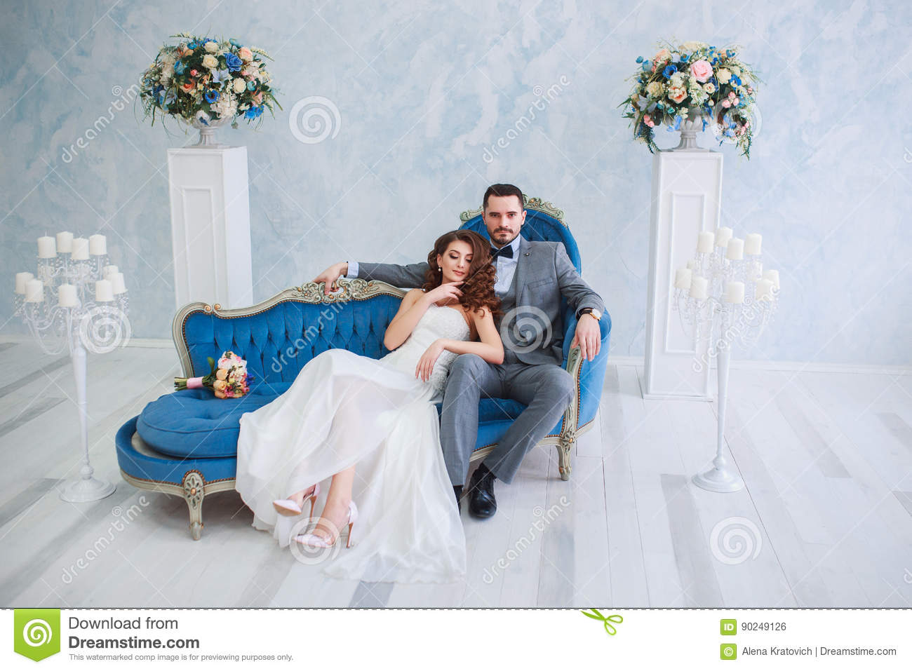 Bride In Beautiful Dress And Groom In Gray Suit Sitting On Sofa ...