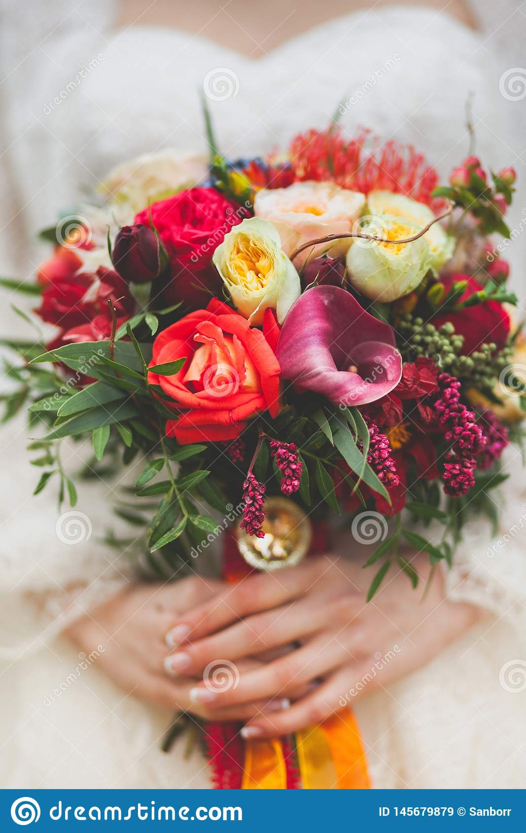 The bride in a beautiful white wedding dress holds a beautiful autumn wedding bouquet. Beautifully decorated multi-colored bouquet