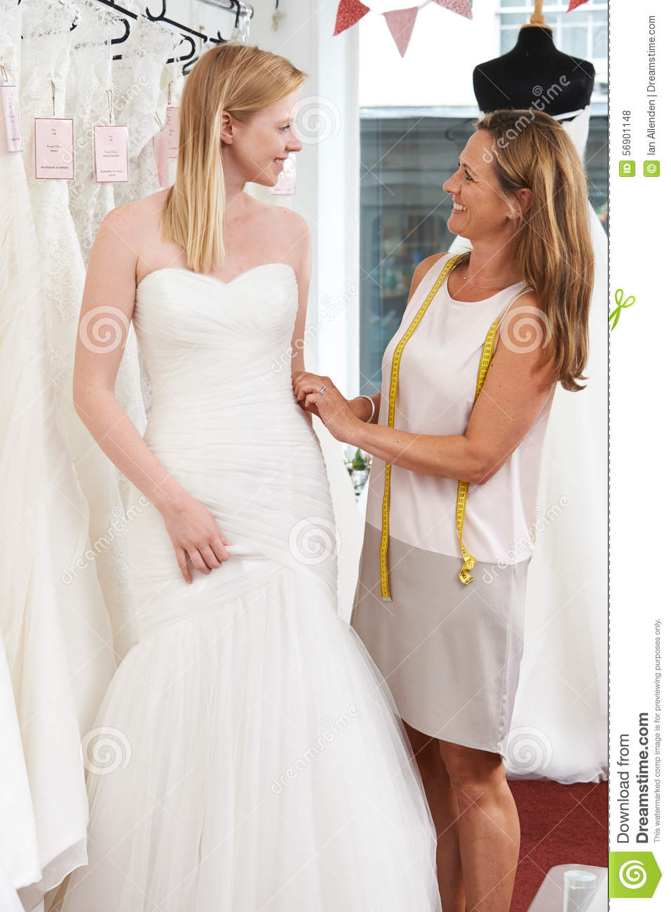 Bride being fitted for wedding dress by store owner stock for Wedding dress in stock