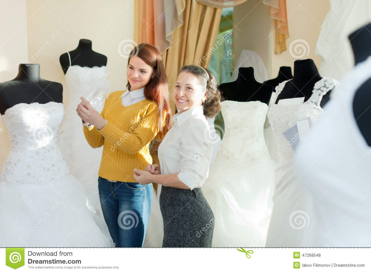 Wedding Photography Consultant: Bride Chooses Bridal Outfit At Wedding Store Stock Photo