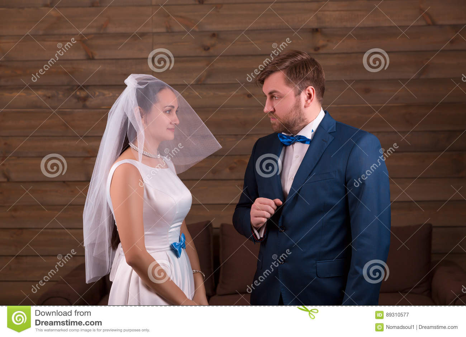 Bride in dress and veil against groom in suit