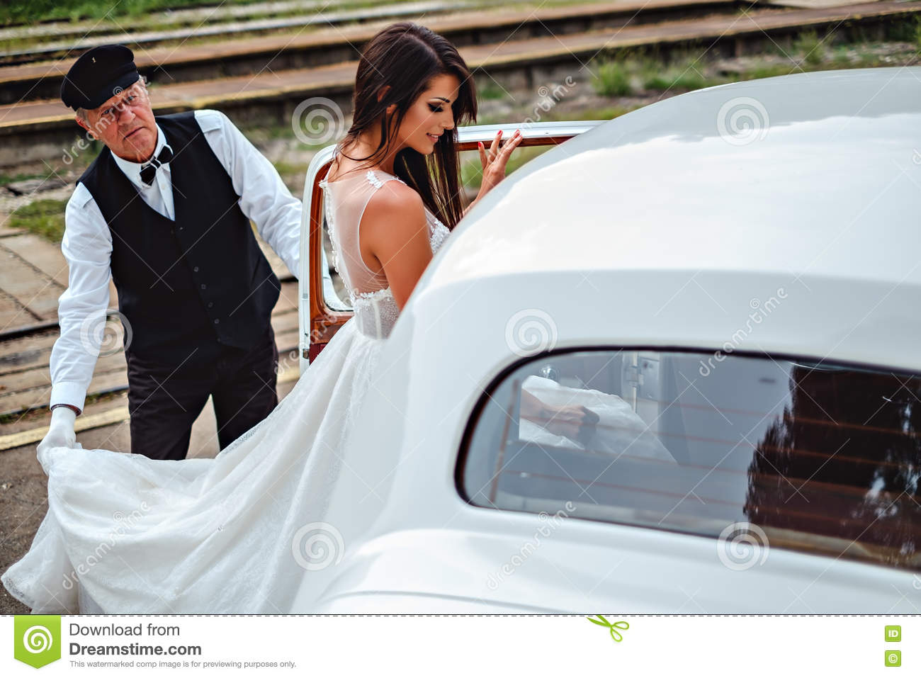 Bride entering classic car and driver holding dress