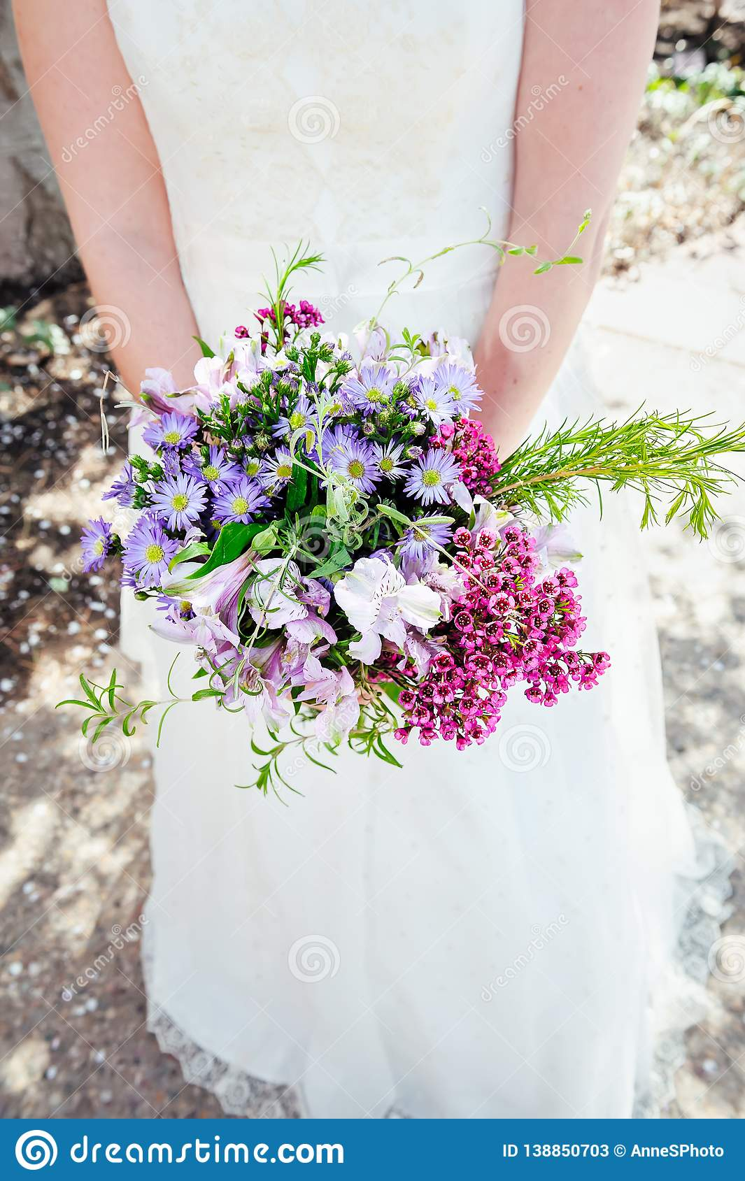 A Bride Holds A Bouquet Of Purple And Pink Wildflowers Stock Image Image Of Background Elegant 138850703