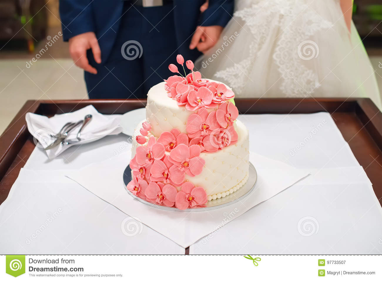 Bride And Groom Cutting Their Wedding Cake Decorated With Orchids ...