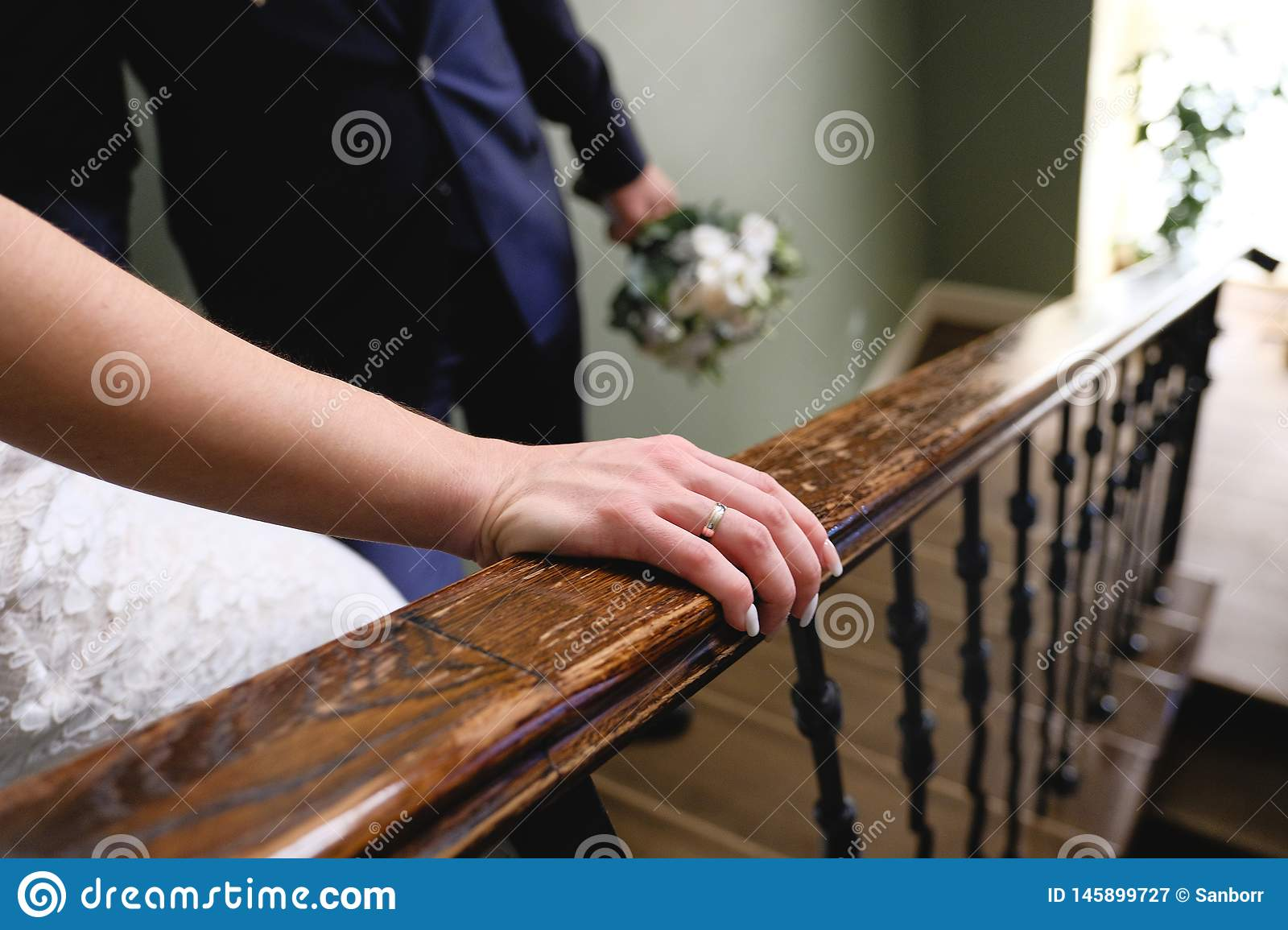 The bride and groom down the stairs, the bride`s hand close-up. Wedding day