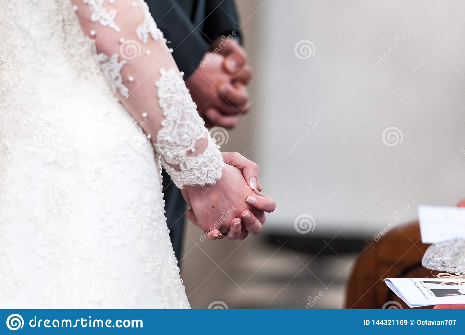 Bride and groom folding hands in church