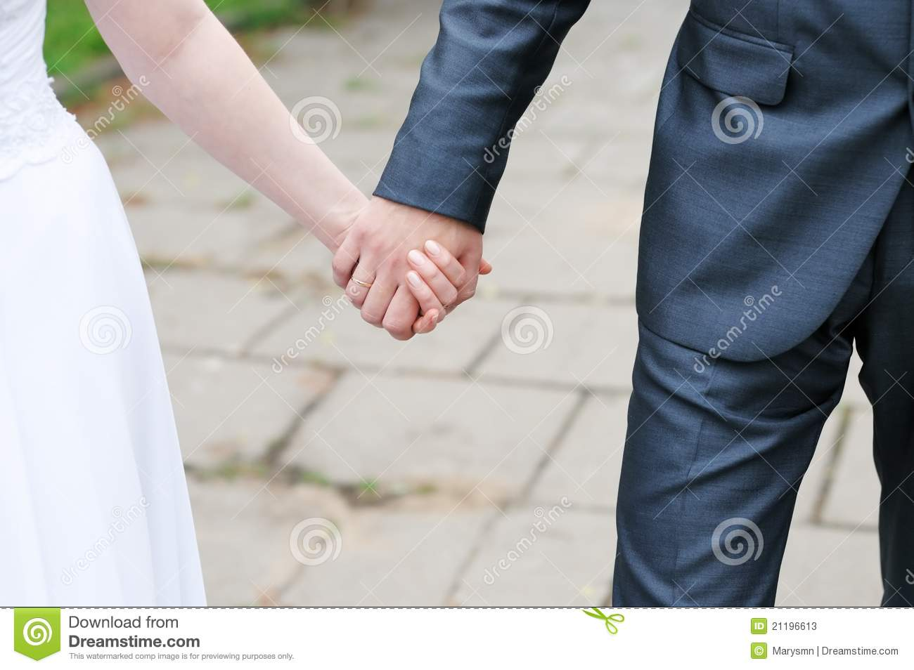 Bride and groom holding each others hands