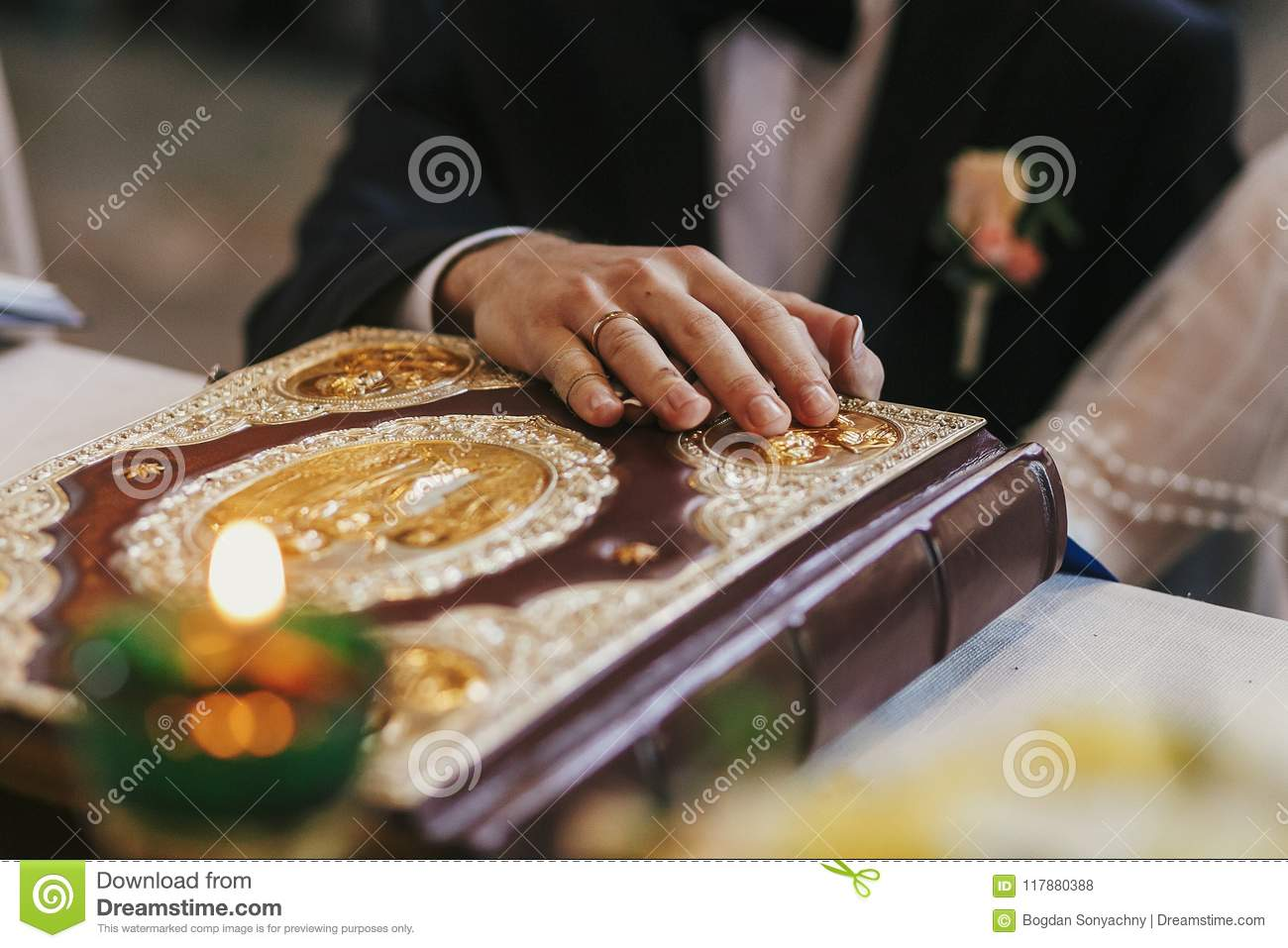 bride and groom holding hands on golden bible on holy altar during wedding ceremony in church, exchanging oaths. spiritual moment