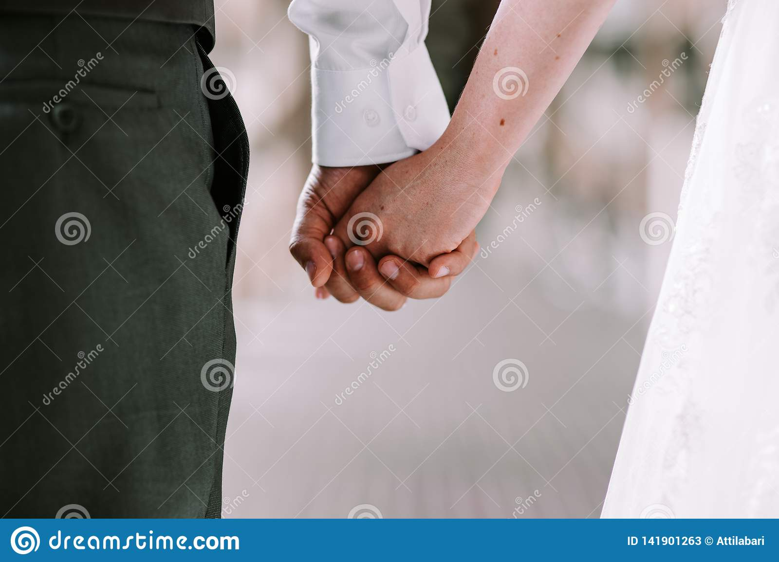 Bride and groom holding hands while walking
