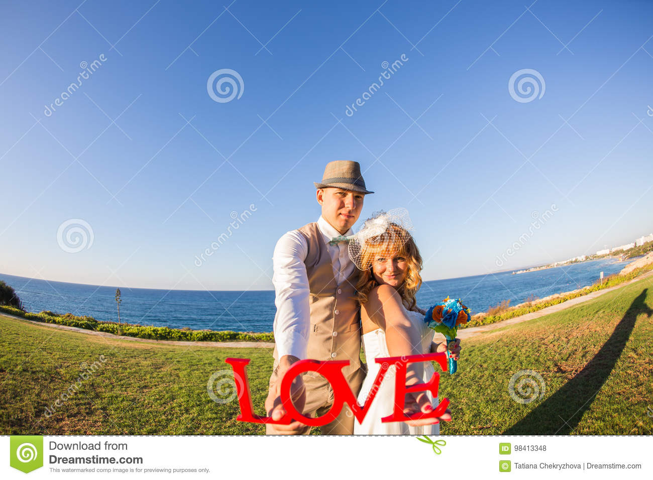 bride and groom holding the letter word love