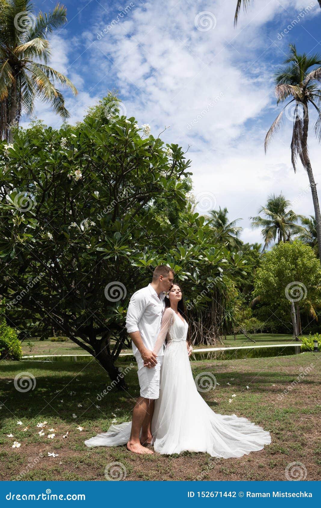 Bride and groom hug around an exotic flowering tree
