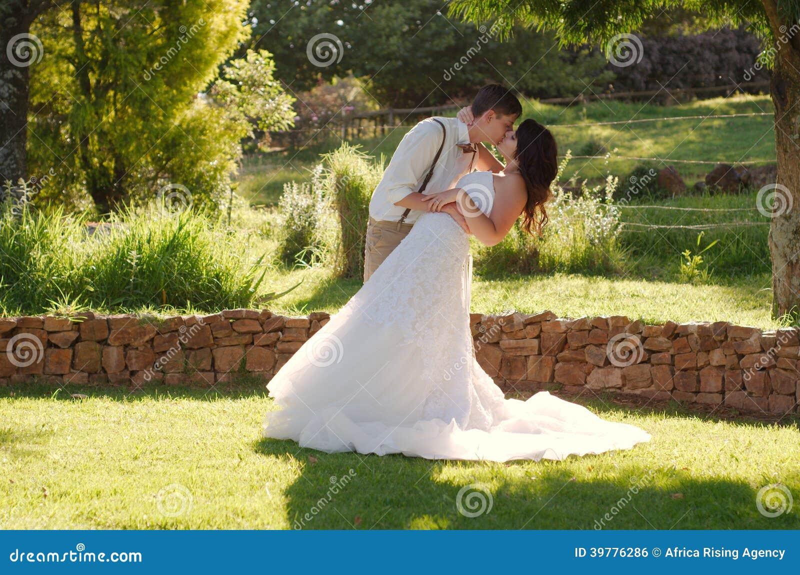 Bride and groom kissing in garden wedding