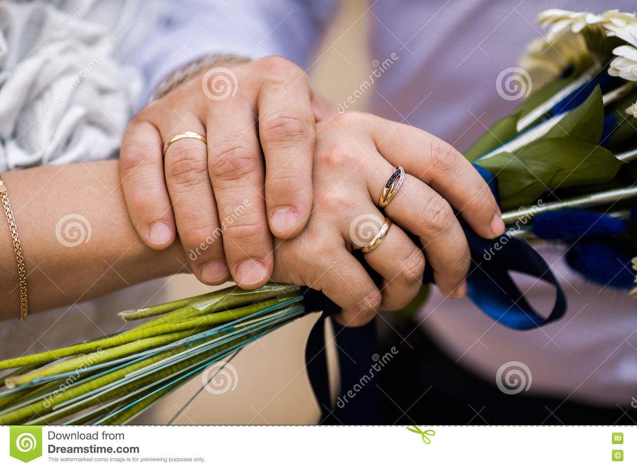 Bride And Groom Next To Wedding Rings On Their Hands Male And