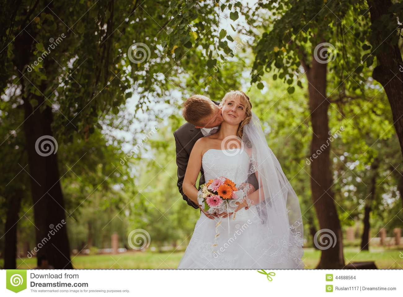 Bride and groom in a park kissing.couple newlyweds bride and groom at a wedding in nature green forest are kissing photo