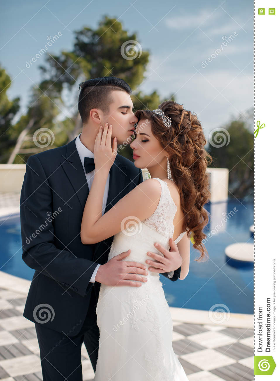 Download The Bride And Groom Beside Pool With Blue Water Stock Photo