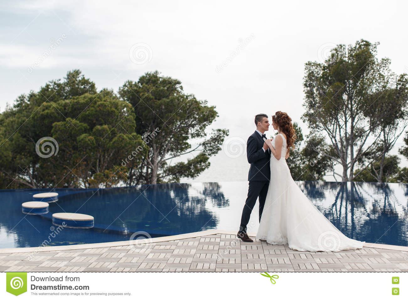 eb62ed582 The Bride And Groom Beside The Pool With Blue Water Stock Photo ...
