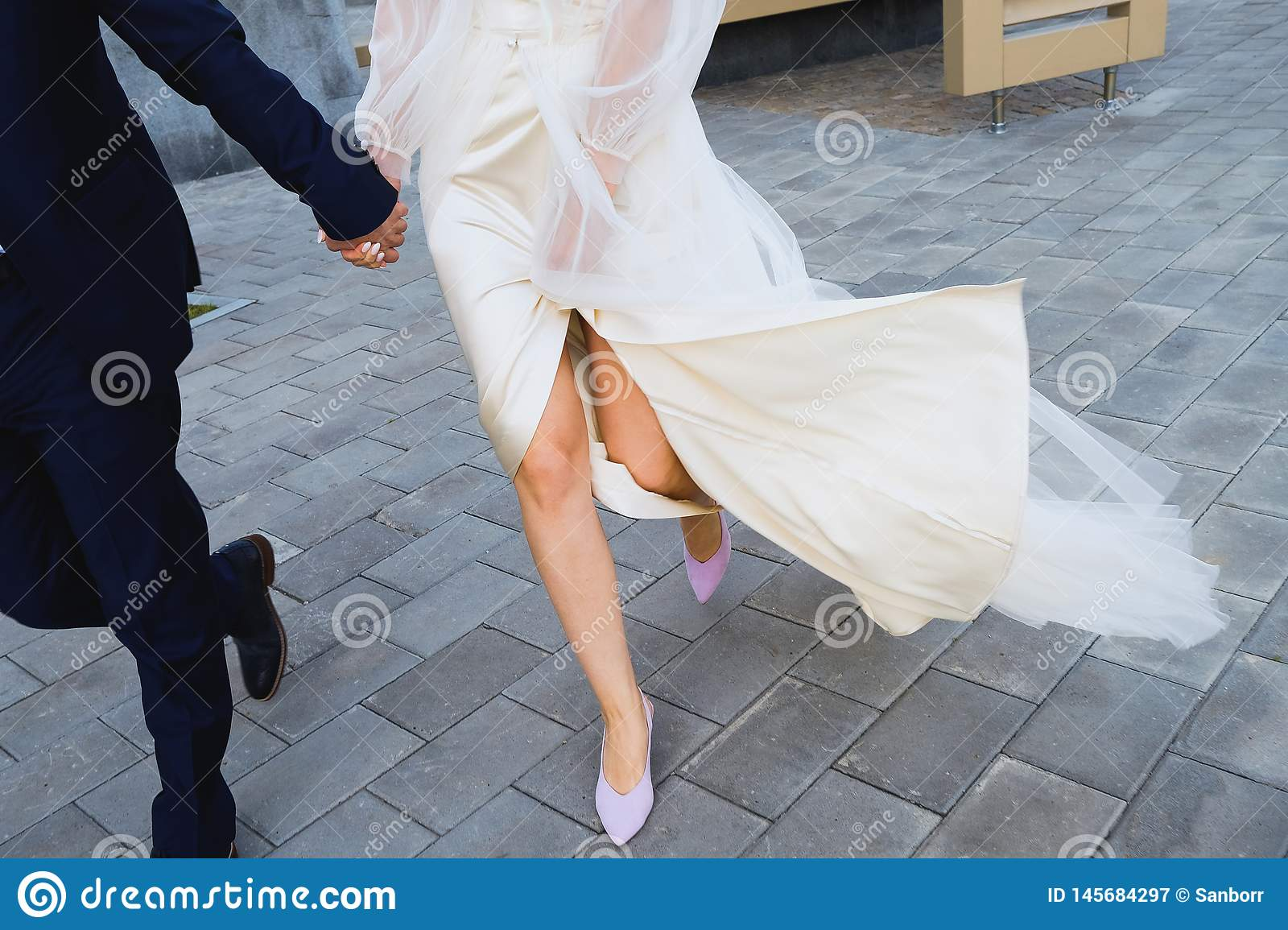 The bride and groom are on the sidewalk, legs close-up