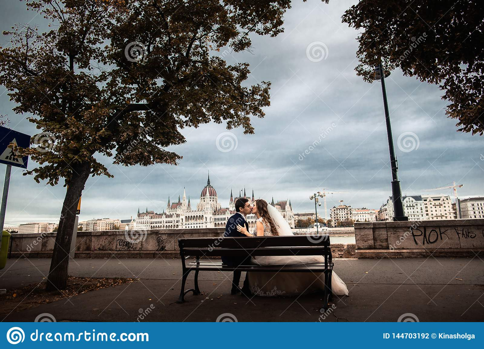 The bride and groom sitting on the bench near the river in the old city. Weeding in Budapest