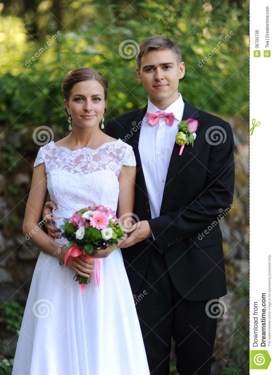 Bride and groom stand in park