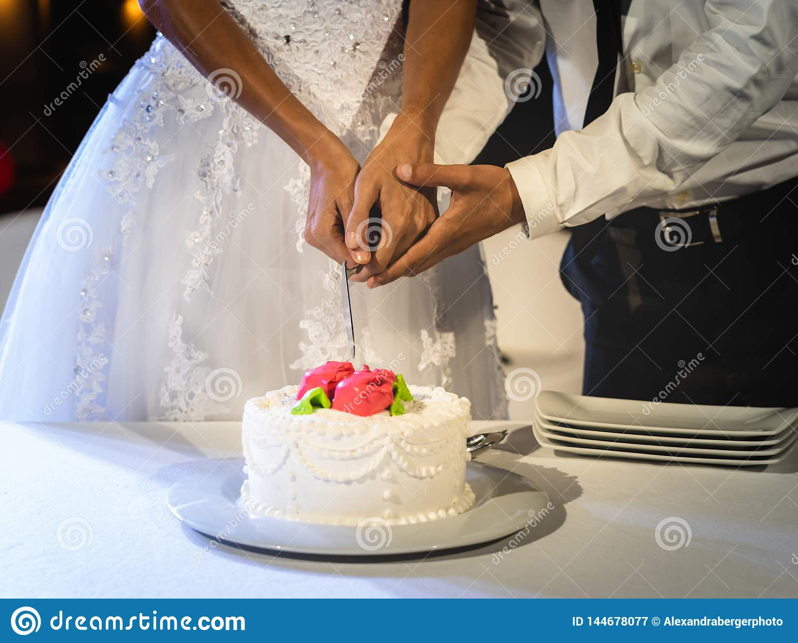 Bride and groom together cut cake at their wedding