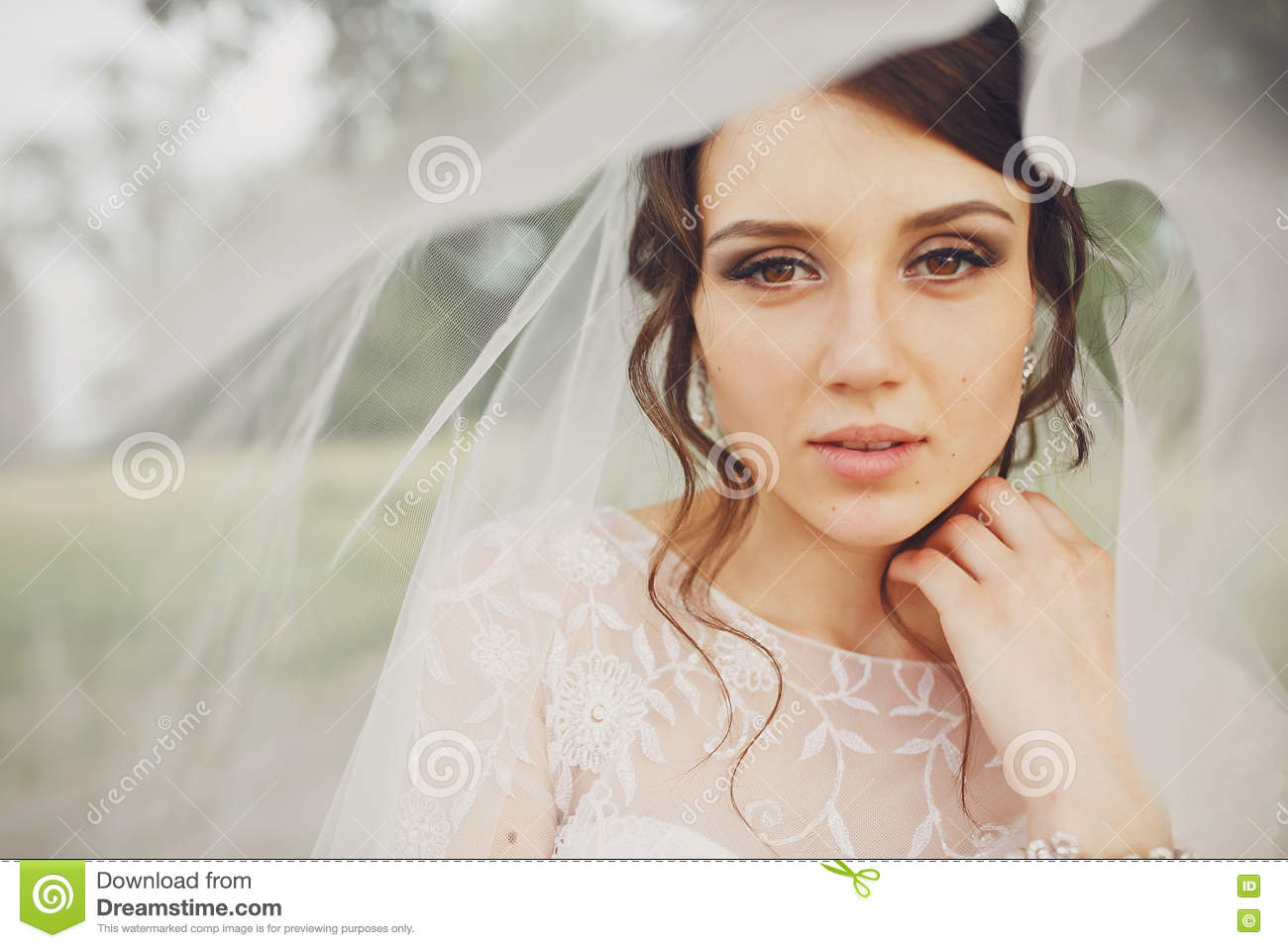 Bride with hazel eyes looks marvelous standing under a veil