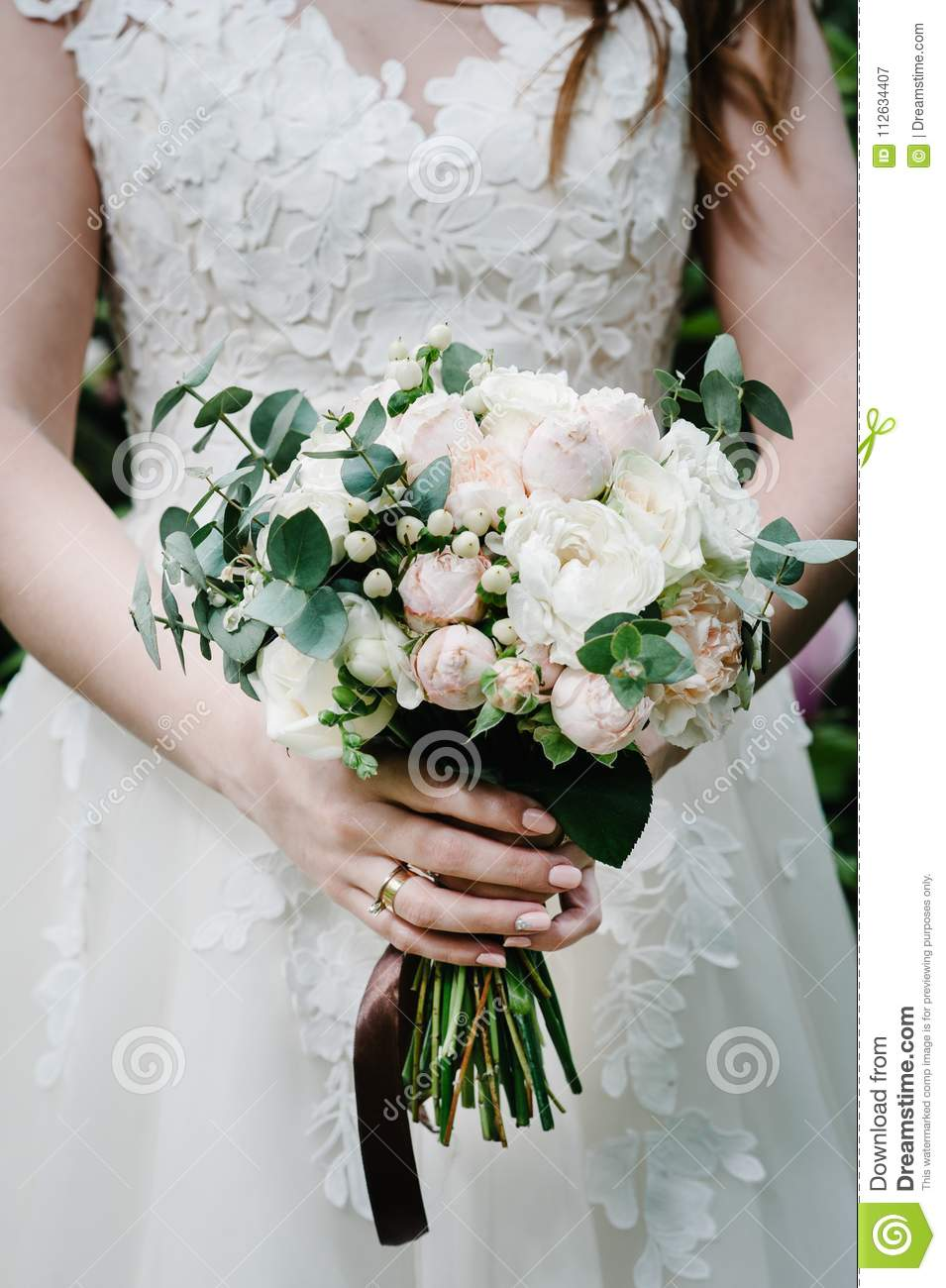 The Bride Holding A Beautiful Wedding Bouquet Of Pastel Pink