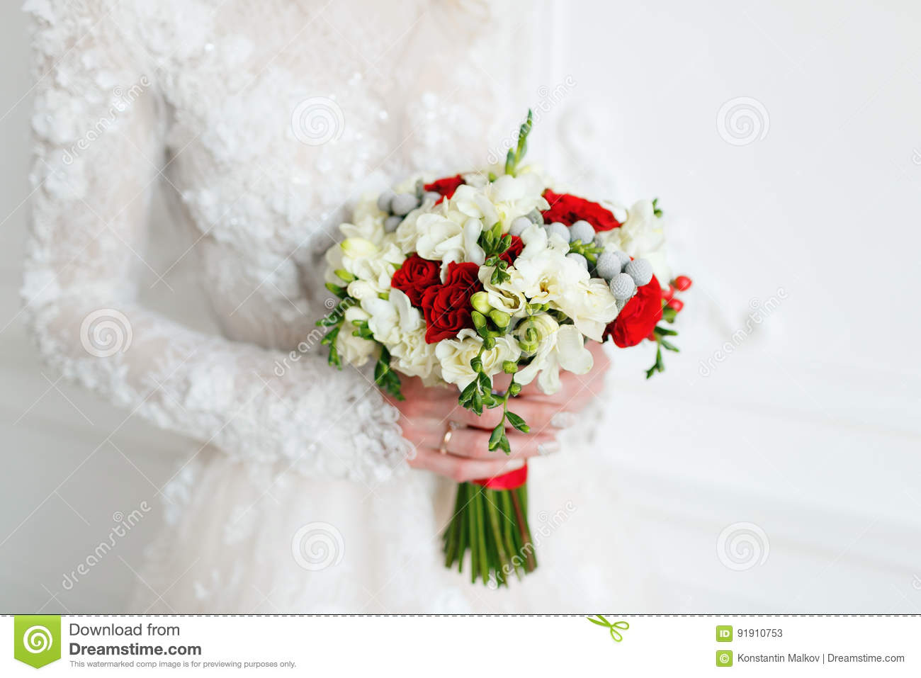 bride holding bridal bouquet close up red and white roses freesia