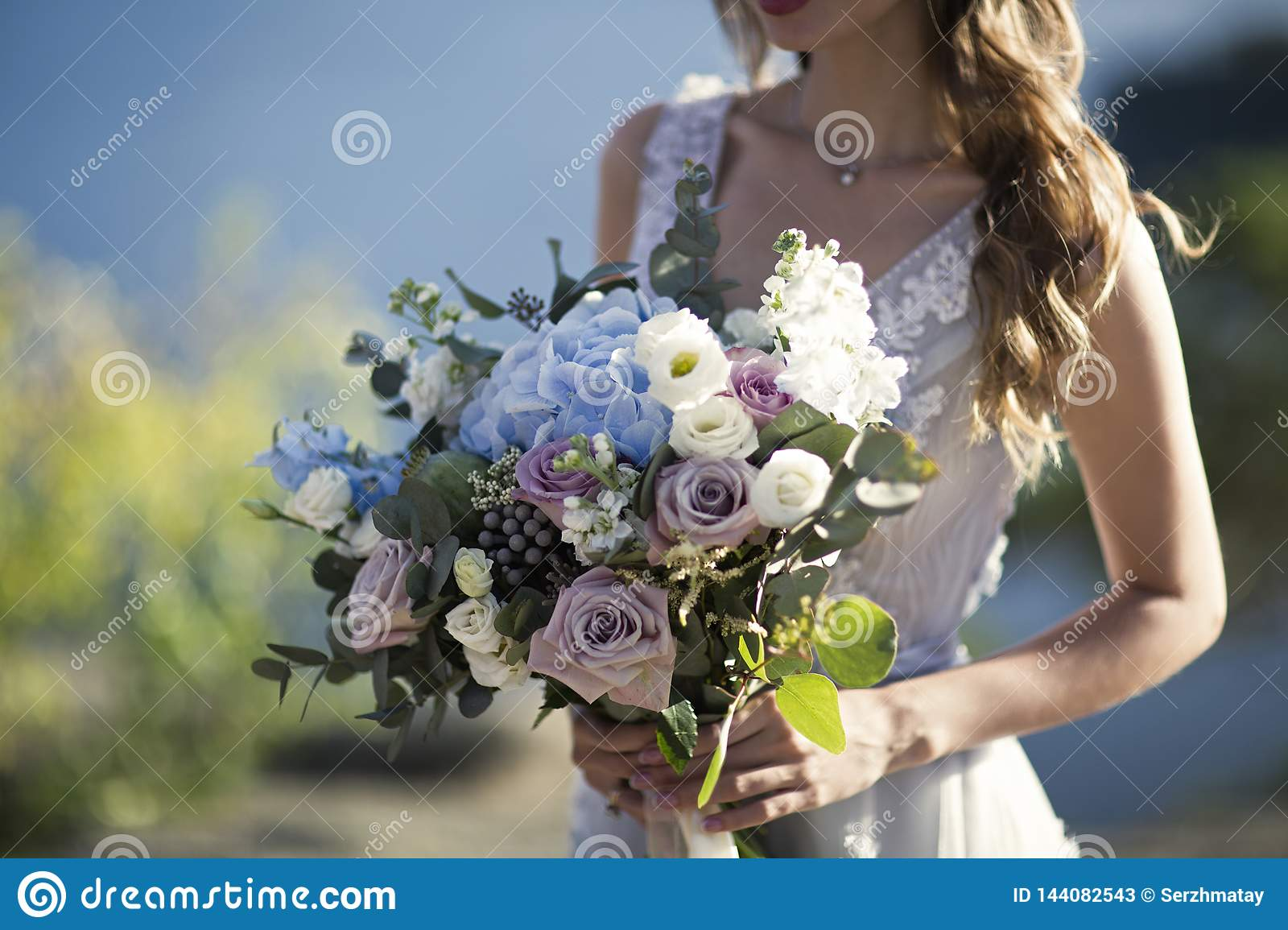Bride holds wedding bouquet on nature background