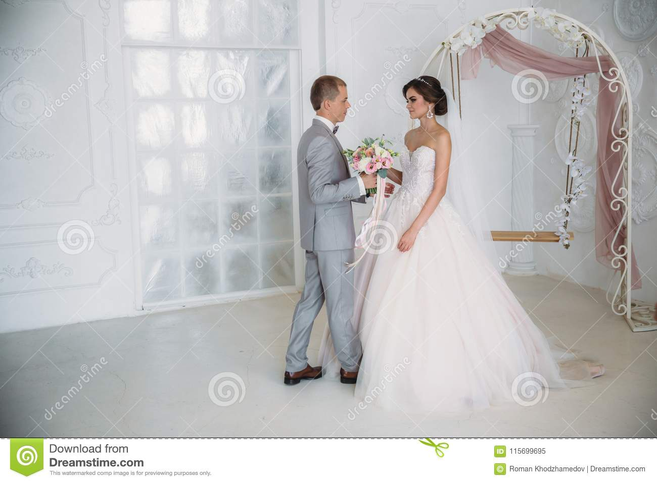 The bride hugs the groom and holds a bouquet of flowers in her hands. A beautiful couple of newlyweds on a wedding day