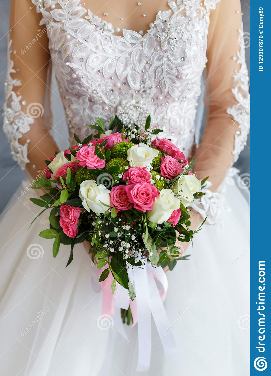 Bride In A Lace Dress Holding A Wedding Bouquet Of White And Pink