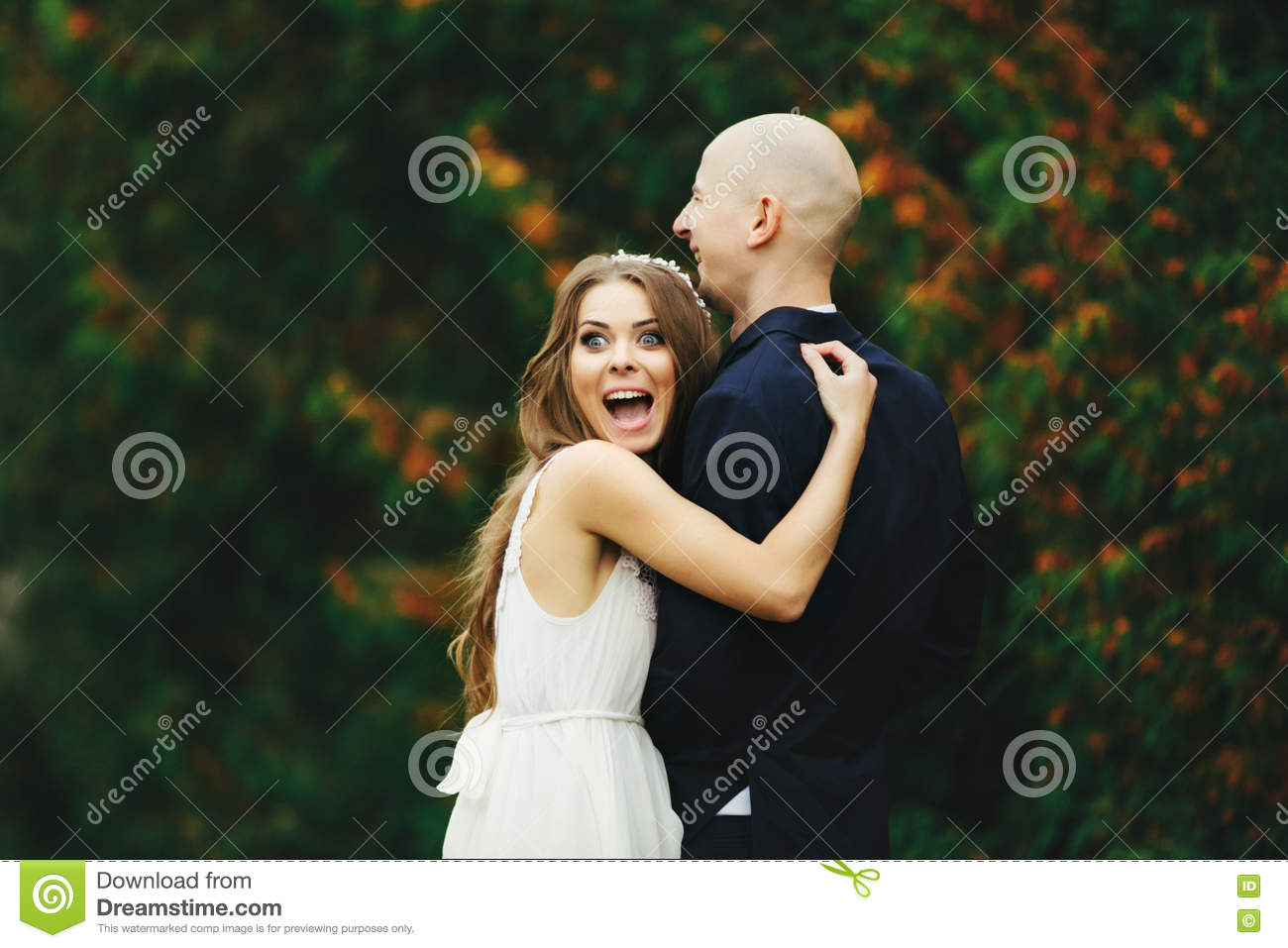 Bride looks funny with eyes open wide while she hugs a groom
