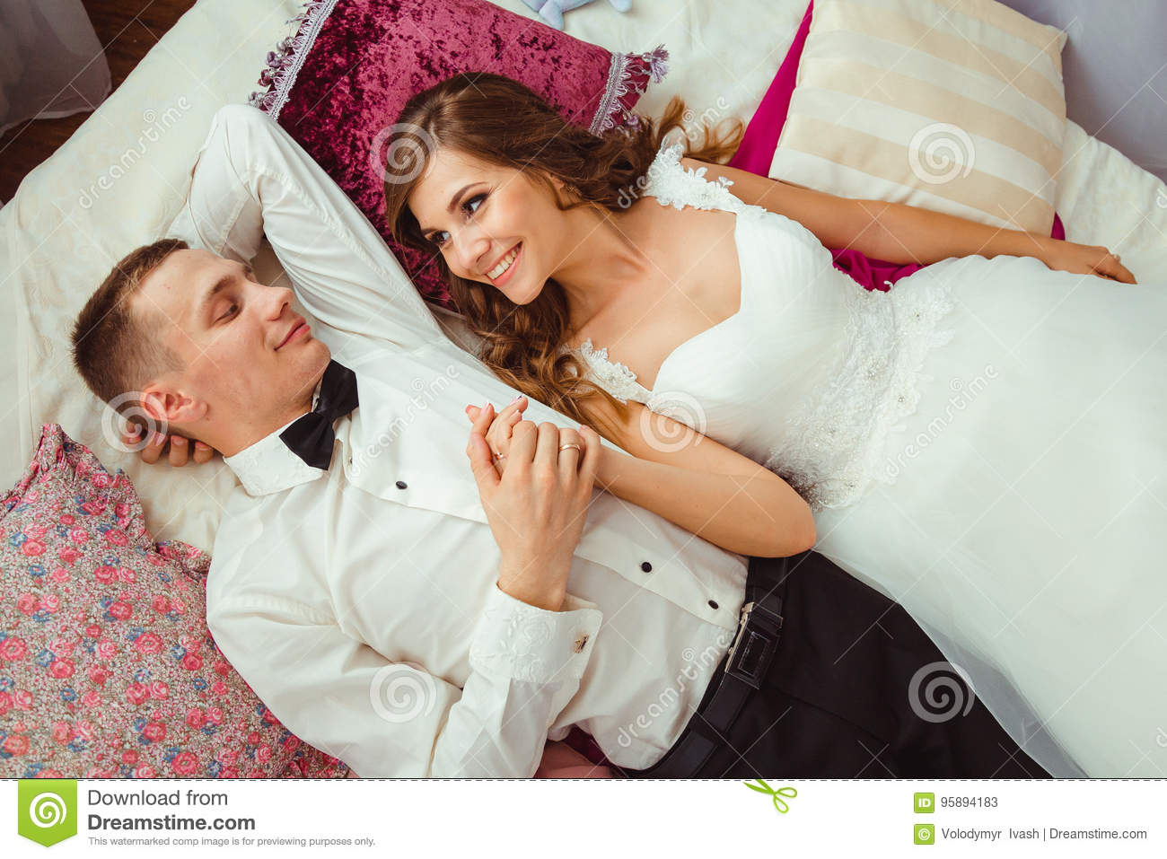 Bride looks at her handsome groom while lying on the bed