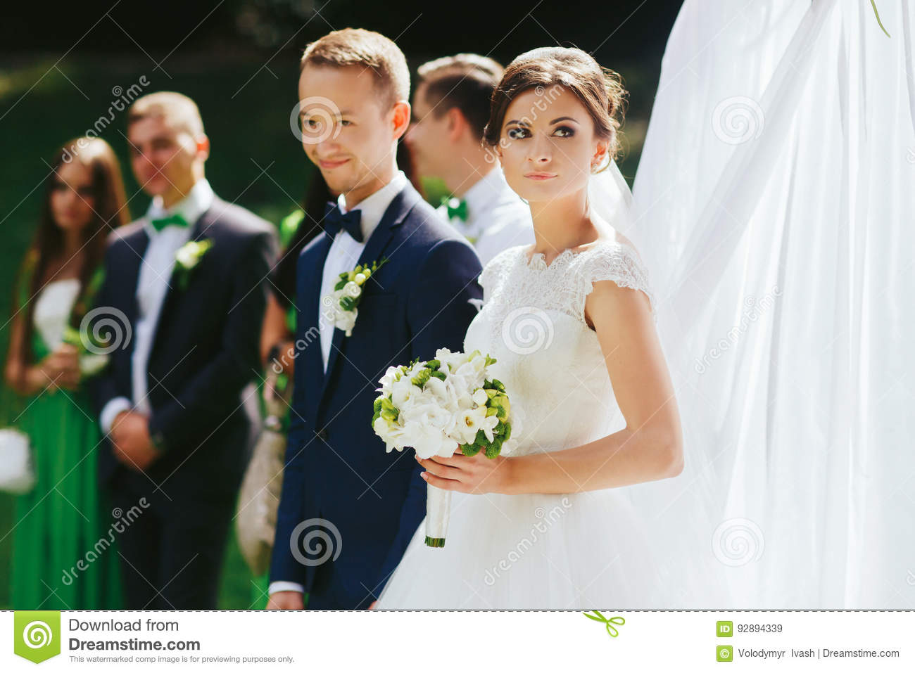 Bride looks up in the sky standing with groom behind an altar