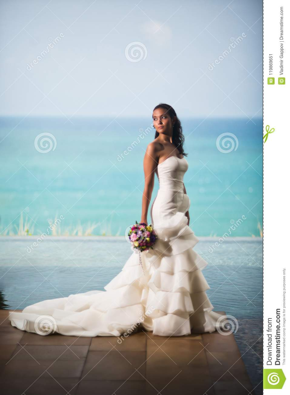 Bride in a luxurious white dress stands on the background of the ocean and looks away