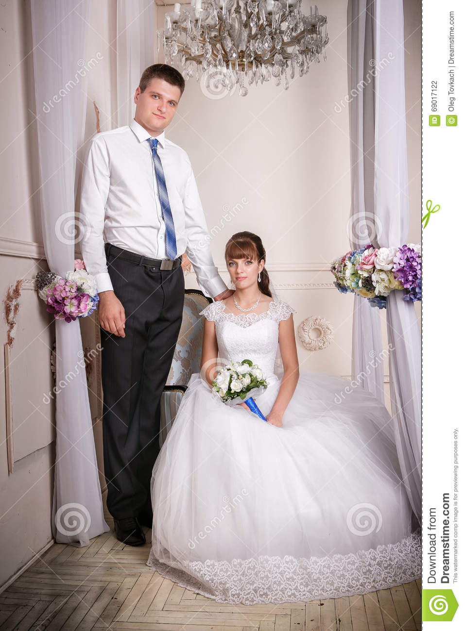The bride sits in a chair and the groom stands near bride in the room