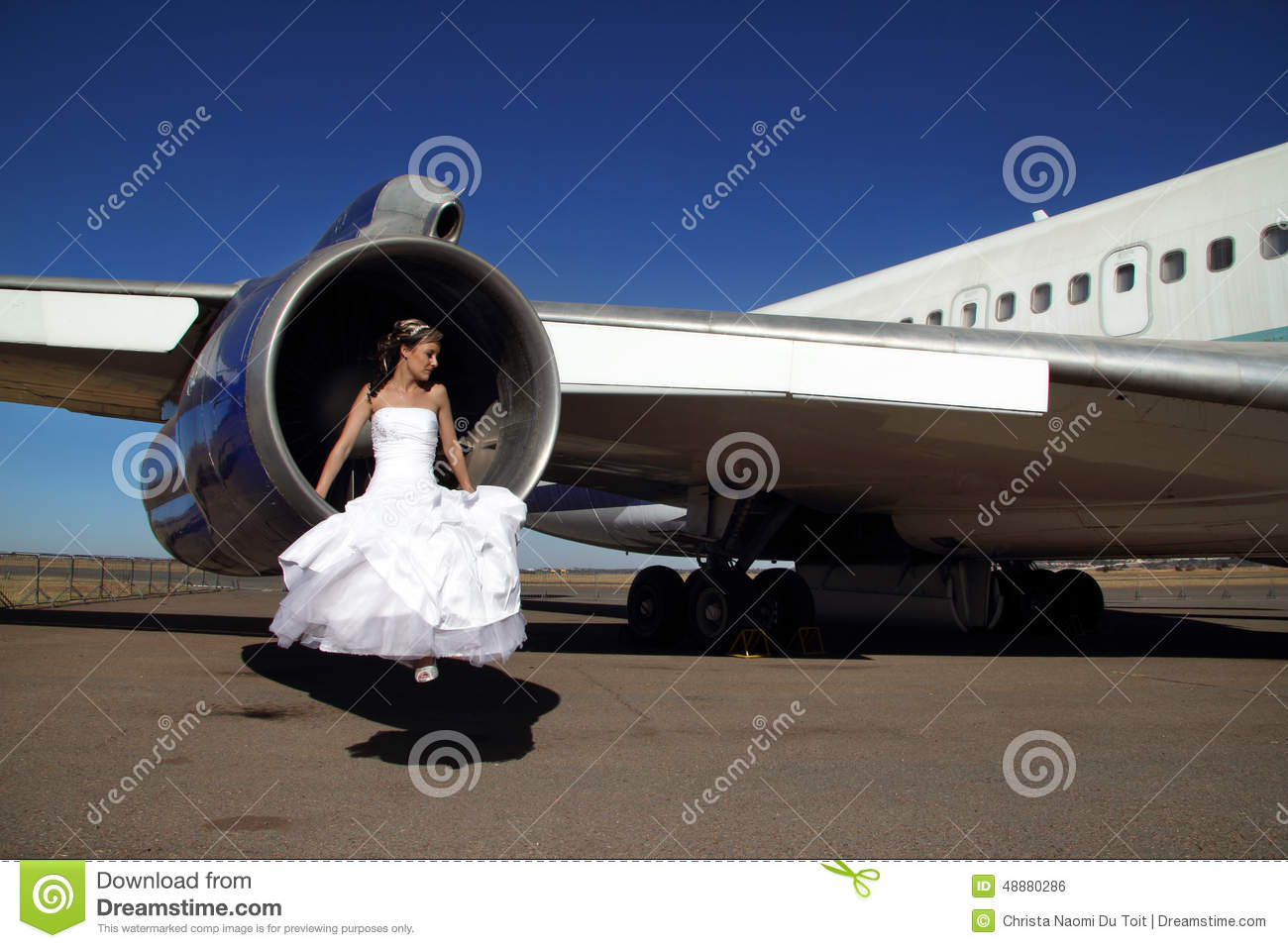 Bride sitting in engine of retired commercial airplane for Wedding dress on plane