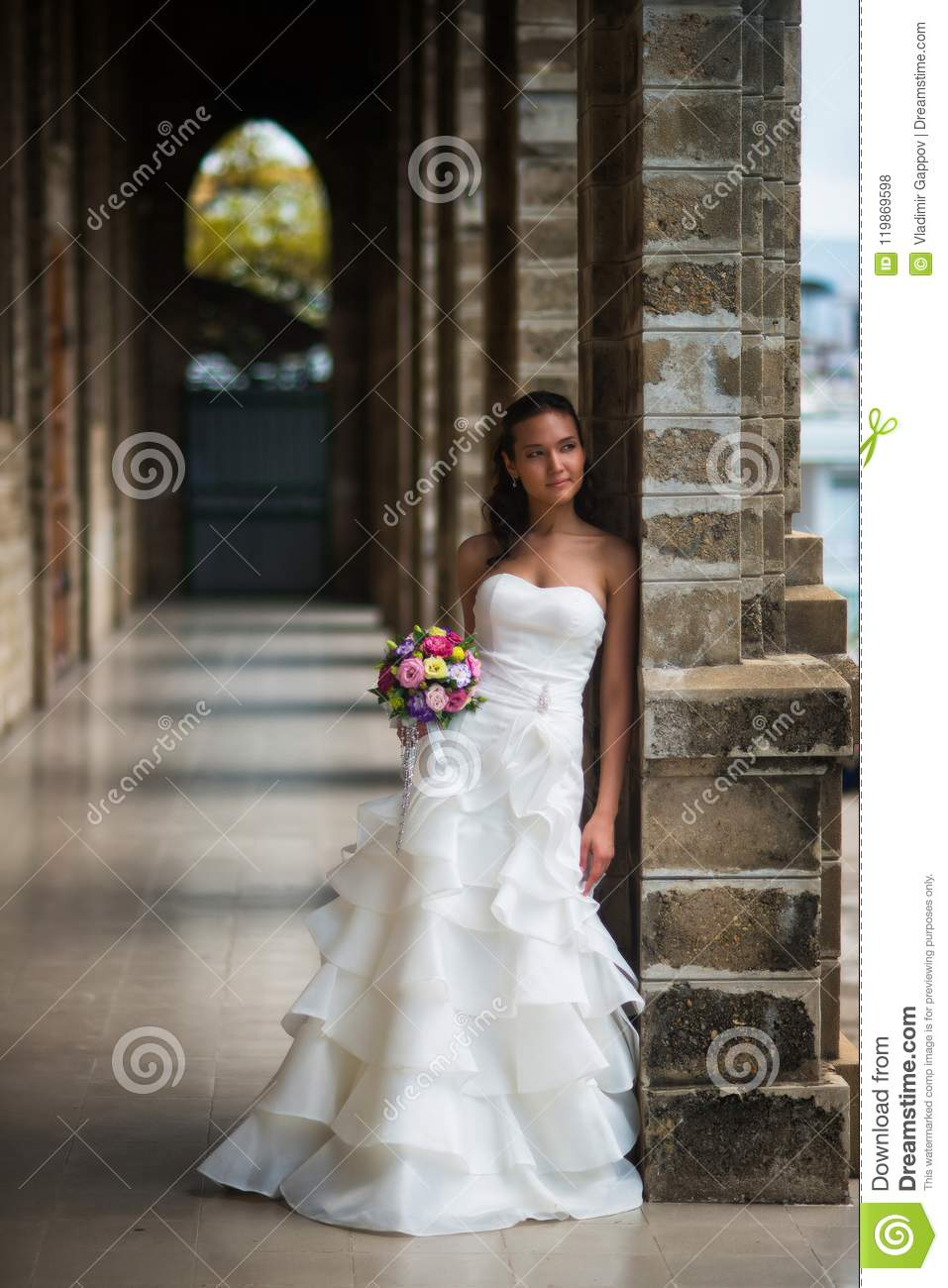 Bride stands in a gallery of stone walls in a beautiful white wedding dress with a bouquet of flowers and looks away